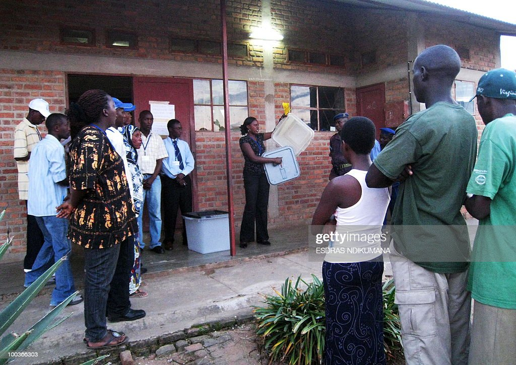 A poll worker shows people wanting to vote (R) an empty ballot box moments before the polling station opened on May 24, 2010 in the capital Bujumbura. Local polls kicked off on May 24 in Burundi, the first phase of an electoral marathon set to put the small, war-scarred African nation's peace deal and democratic credentials to the test. Polling stations opened at 6:00 am (0400 GMT), with some 3.5 million voters called to pick local councillors in a ballot seen a key test for presidential and legislative elections due in June and July respectively.