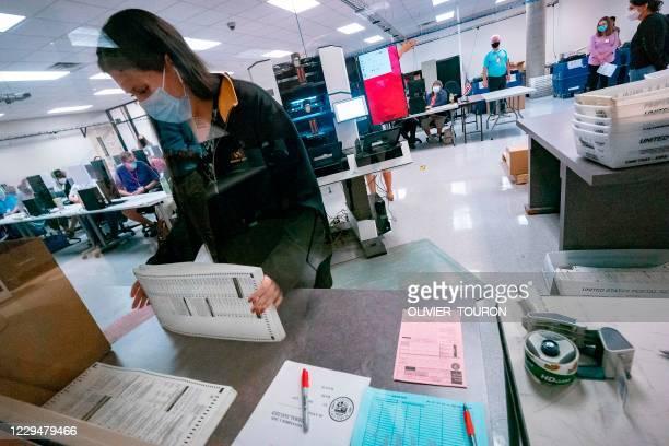 Poll worker sorts ballots inside the Maricopa County Election Department in Phoenix, Arizona on November 5, 2020 - Former vice president Joe Biden,...