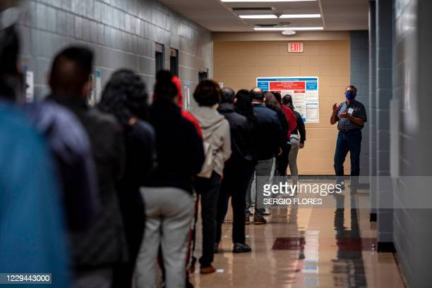 Poll worker talks to a line of voters on election day on November 3, 2020 in Austin, Texas. - The United States started voting Tuesday in an election...