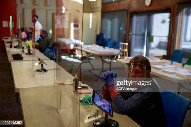 Poll worker waits for voters at the Unitarian Universalist church in Bloomington. Polling stations across the United States open for voters to cast...