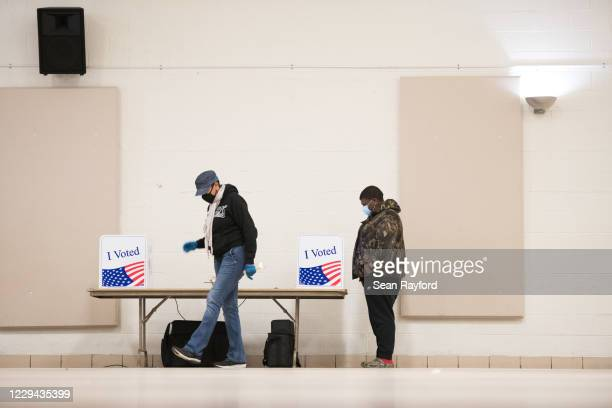Poll worker walks across the room as a voter looks at their choices on November 3, 2020 in Columbia, South Carolina. After a record-breaking early...
