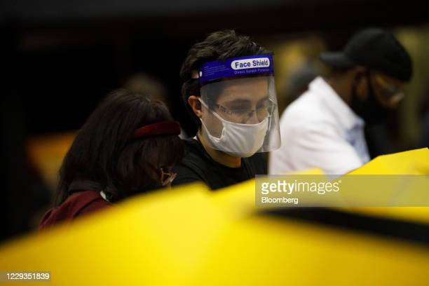 Poll worker wearing a protective face shield helps a voter with an electronic Voting Solutions for All People ballot marking machines at an early...