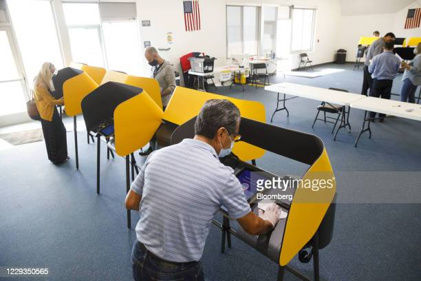Poll worker wearing a protective mask sanitizes an electronic Voting Solutions for All People ballot marking machine at an early voting polling...