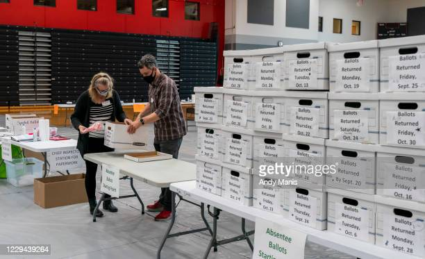 Poll workers Angela and Zach Achten check-in a box of absentee ballots in the gym at Sun Prairie High School on November 3, 2020 in Sun Prairie,...