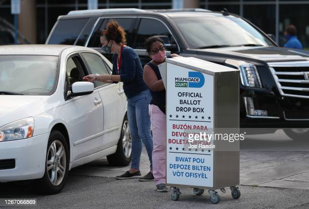 Poll workers at the MiamiDade County Elections Department deposit peoples' mail in ballots into an official ballot drop box on primary election day...