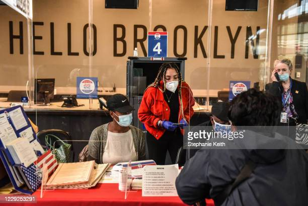 Poll workers check in a voter at the Barclays Center during early voting for the US Presidential election on October 24 2020 in the Brooklyn borough...