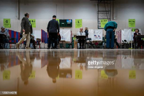Poll workers check in voters at a polling station at David R Cawley Middle School on February 11 2020 in Hookset New Hampshire New Hampshire holds...