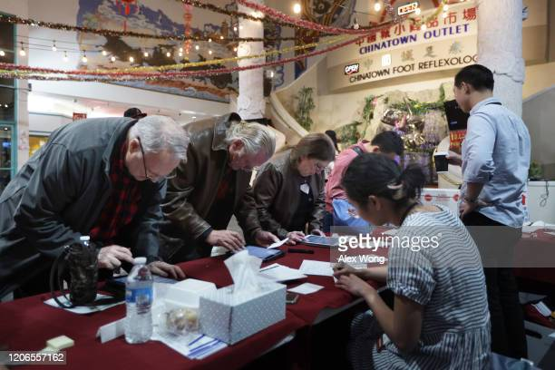 Poll workers check voters in during early voting in the Nevada Caucus at Chinatown Plaza Mall February 15 2020 in Las Vegas Nevada The first time in...