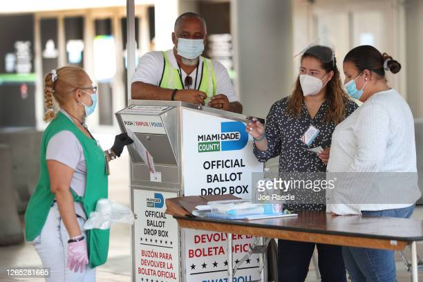 Poll workers help a voter put their mailin ballot in an official MiamiDade County ballot drop box on August 11 2020 in Miami Florida The secure drop...