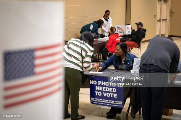 Poll workers help check potentials voters in at the Oasis Shriners Temple polling station during the North Carolina primary on Super Tuesday in...