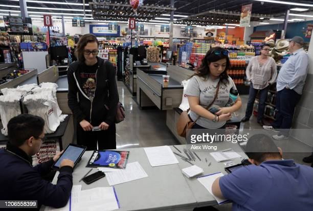 Poll workers help to check voters in during early voting in the Nevada Caucus at Cardenas Market February 15 2020 in Las Vegas Nevada The first time...