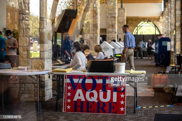 Poll workers help voters inside a polling location on October 13, 2020 in Austin, Texas. The first day of voting saw voters waiting hours in line to...