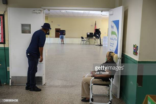 Poll workers look on as a voter fills out his ballot on primary election day on August 18, 2020 in Miami, Florida. Voters are casting ballots in...