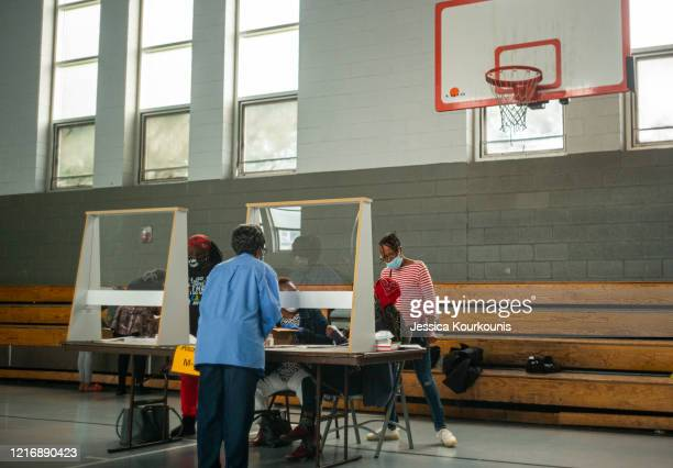 Poll workers sit behind plexiglass barriers during primary elections on June 2, 2020 in Philadelphia, Pennsylvania. Voters in seven states are...