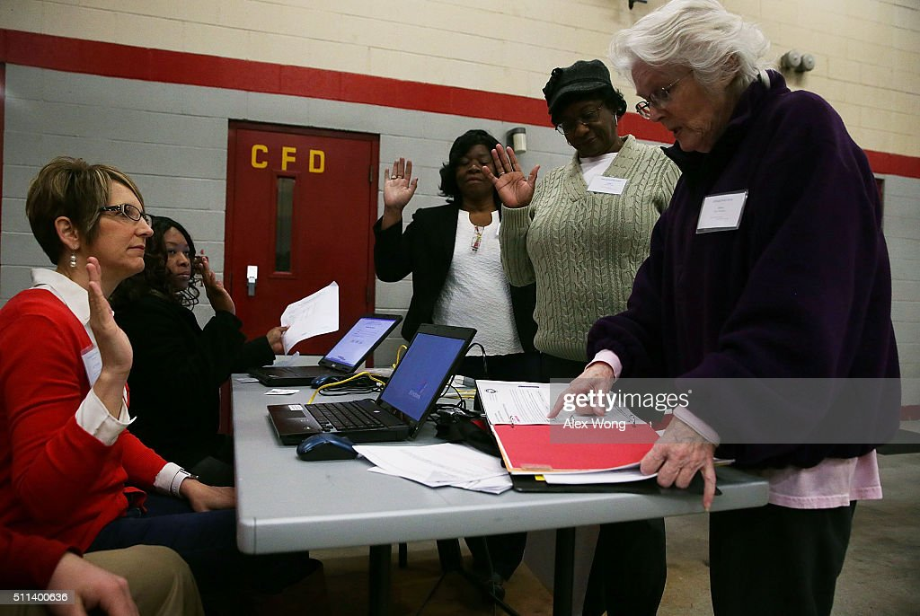 Poll workers take the oath prior to opening the door for voters at a polling station at Shandon Fire Station February 20, 2016 in Columbia, South Carolina. Residents of South Carolina picked their candidate in the state Republican primary today.