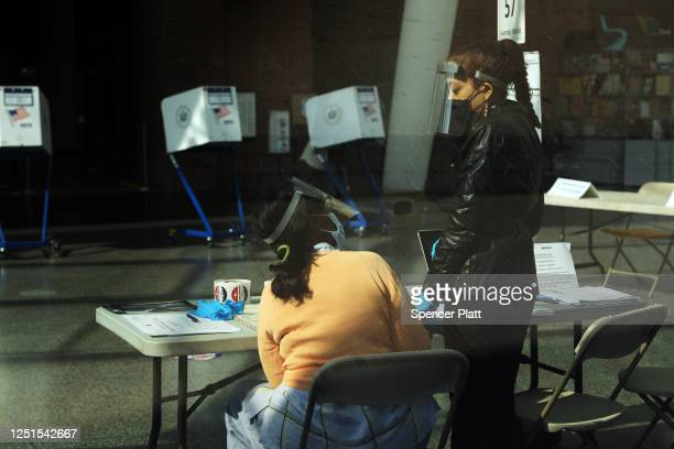 Poll workers wait for voters during a primary election for city state and federal offices at the Brooklyn Museum on June 23 2020 in New York City The...