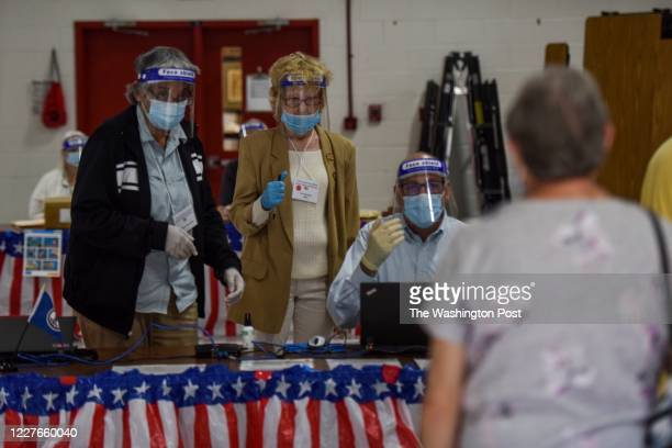 Poll workers welcome voters as Virginia voters take to the polls to cast ballots in an unusual primary election shaped by the coronavirus pandemic at...