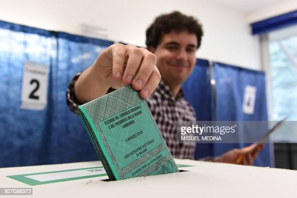 TOPSHOT A polling advisor casts a ballot on March 4 2018 at a polling station in Milan Italians vote today in one of the country's most uncertain...