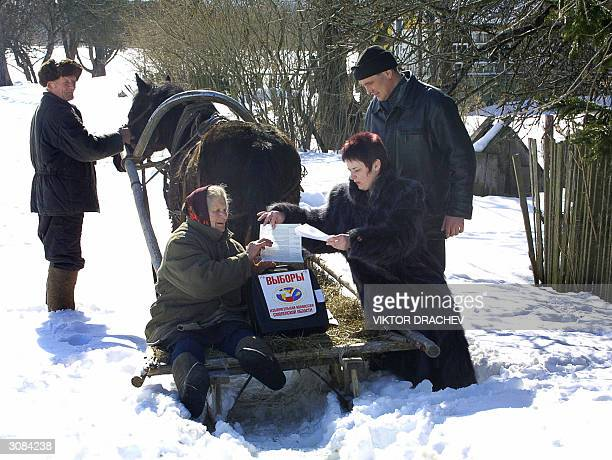 Polling box is brought on a sledge pulled by a horse, to Nadezhda Sharpaeva from Rytino village, some 70 kilometers west of Smolensk to cast her vote...