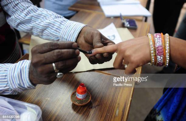 A polling officer mark in a finger of a voter as they arrive to cast their votes for the 4th phase of assembly election in Allahabad