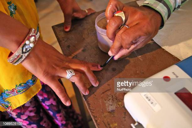 A polling officer marks a voters' finger with ink as she casts her vote at a local polling station for the state Assembly elections at Raisar Village...