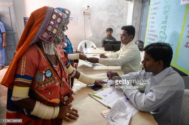 A polling officer marks the finger of Indian lambadi tribeswomen before they vote at a polling station during India's general election at Pedda...