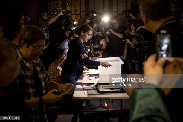 A polling officer opens one of the first ballot boxes for counting at Escola Industrial of Barcelona school polling station as the Catalan government...