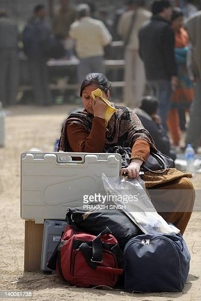 Polling officer sits with electronic voting machines as she waits for transportation at an EVM distribution centre in Ghaziabad, Uttar Pradesh on...