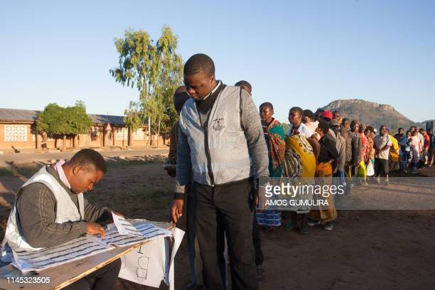 A polling officer watches as his colleague checks his details before he votes at Goliati Primary School in Goliati village the home of Malawi's...