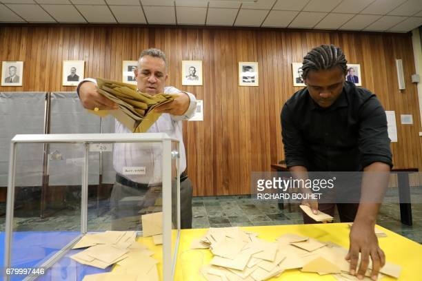 Polling officials take off the ballots from the ballot box in order to count them on May 7 in SaintDenis de la Reunion on the French Indian Ocean...