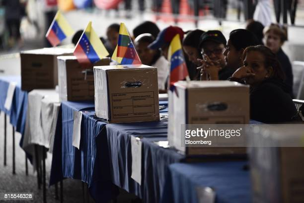 Polling officials wait for voters during a symbolic Venezuelan plebiscite in Caracas Venezuela on Sunday July 16 2017 Voting is under way in the...