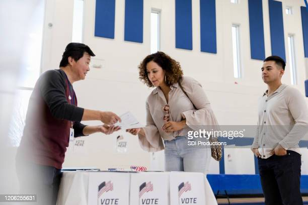 polling place volunteer explains ballot to voter - polling place stock pictures, royalty-free photos & images