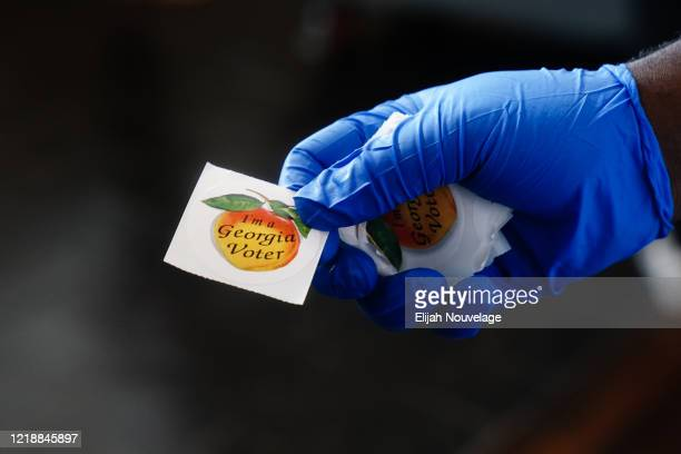 "Polling place worker holds an ""I'm a Georgia Voter"" sticker to hand to a voter on June 9, 2020 in Atlanta, Georgia. Georgia, West Virginia, South..."