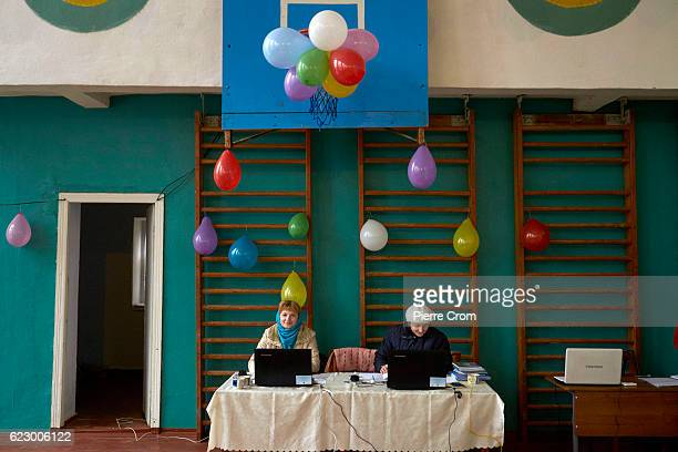 Polling staff wait to register voters at polling station on November 13 2016 in Calfa Moldova Moldovans cast their votes on Sunday in a presidential...