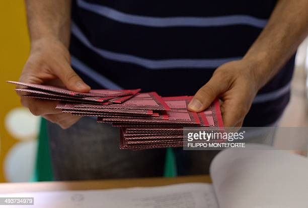 A polling station attache counts European parliamentary elections ballot slips at a polling station in Rome on May 25 2014 Europeans vote for a new...