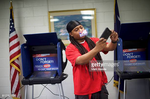 Polling station clerk Wryan Sarieant takes a selfie with his name tag across his mouth at the Cordova Town Hall polling precinct for the South...