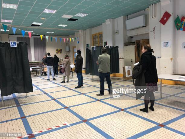 Polling station in Paris, France for the municipal elections in March 2020 during the coronavirus pandemic and causing COVID-19. Line of electors...