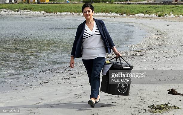 Polling station manager Teresa McCurdy arrives on Rathlin Island off the northeast coast of Northern Ireland on June 22 carrying a ballot box in...