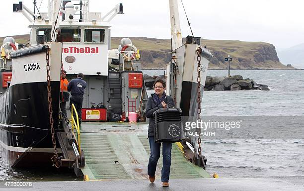 Polling station manager Teresa McCurdy walks off a ferry as she arrives on Rathlin Island off the north east coast of Northern Ireland on May 5...