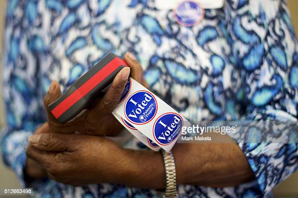 A polling station official holds 'I Voted' stickers at the Prince Hall Masonic Lodge for the South Carolina Democratic Presidential Primary February...