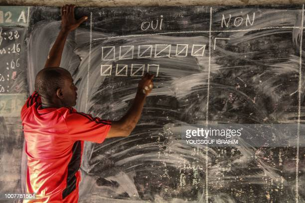A polling station official marks the results on a blackboard at a school in Mutsamoudou in the Anjouan island of the Comoros Archipelago on July 30...