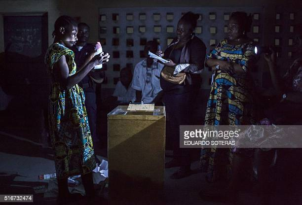Polling station officials at the Pierre Ntsiete Primary School in Brazzaville count ballots at the end of the vote for the presidential election on...