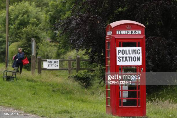 Polling station sign is seen on a telephone box outside the polling station at Rotherwick Hall, west of London, on June 8 as Britain holds a general...