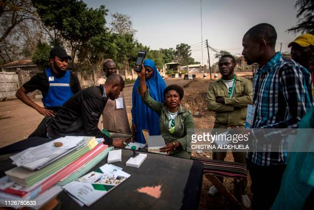 TOPSHOT A polling station worker shows a card reader to waiting voters at a polling station in Kaduna on February 23 as Nigeria votes to elect its...