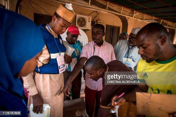 Polling station workers prepare card readers ballot and boxes to start the Election Day at Unguwar Sarki polling station in Kaduna on February 23 as...