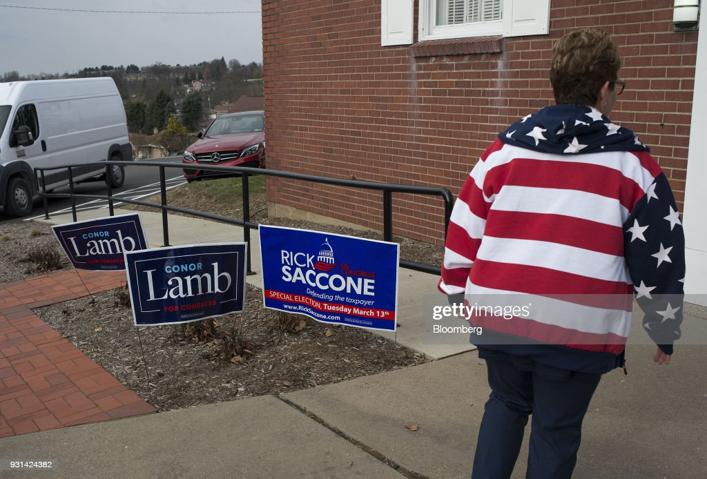 A polling volunteer wearing an American flag sweatshirt walks past campaign signs for Conor Lamb, Democratic candidate for the U.S. House of Representatives, and Rick Saccone, Republican candidate for the U.S. House of Representatives, displayed outside the Mount Vernon Presbyterian Church polling location in McKeesport, Pennsylvania, U.S., on March 13, 2018. Saccone and Lamb are competing in the 18th District, where President Donald Trump won by almost 20 points in the 2016 presidential election, to replace Republican Tim Murphy who resigned last October amid personal scandal. Photographer: Ty Wright/Bloomberg via Getty Images
