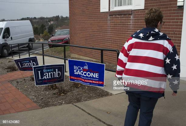 A polling volunteer wearing an American flag sweatshirt walks past campaign signs for Conor Lamb Democratic candidate for the US House of...