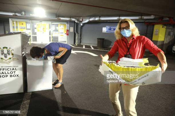A polling worker carries 2020 presidential primary ballots that were dropped off at a post office and brought to a government center to be processed...