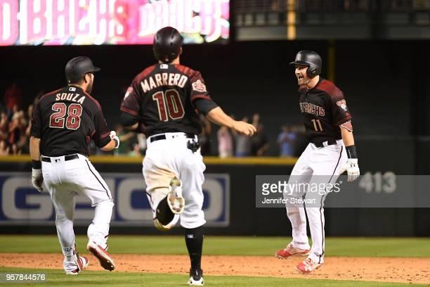 J Pollock of the Arizona Diamondbacks celebrates a walk off single with Steven Souza Jr #28 and Deven Marrero during the MLB game against the Houston...