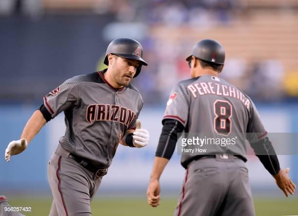 J Pollock of the Arizona Diamondbacks celebrates his two run homerun with third base coach Tony Perezchica to take a 20 lead during the first inning...